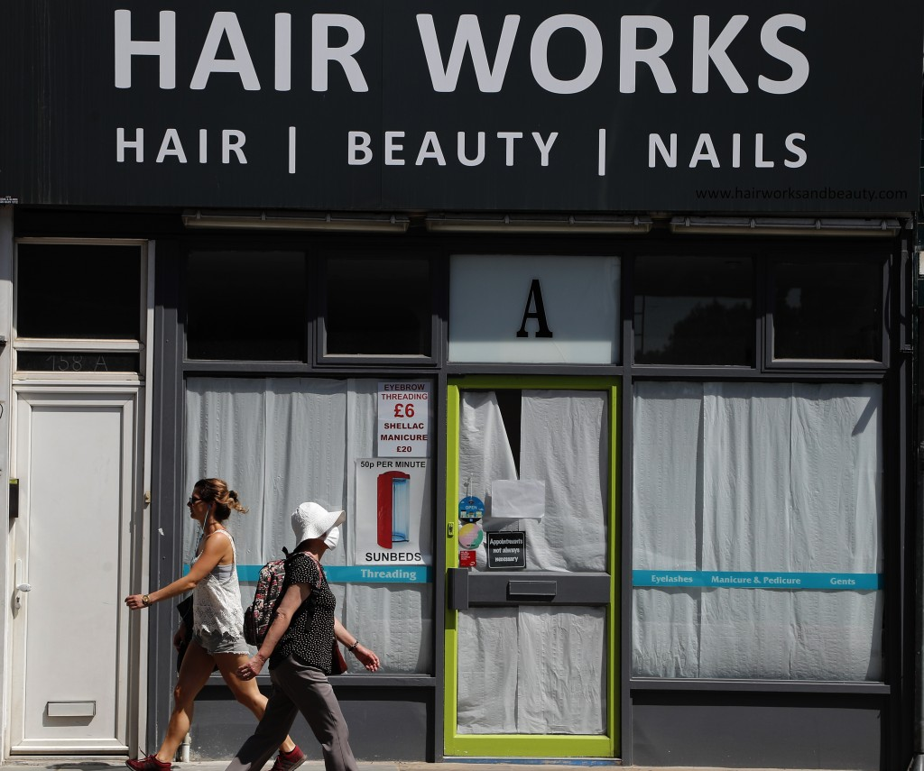 People walk past a closed Hair cutter in London, Tuesday, June 23, 2020.  The closing of restaurants, hair cutters and pubs is expected to be under re...