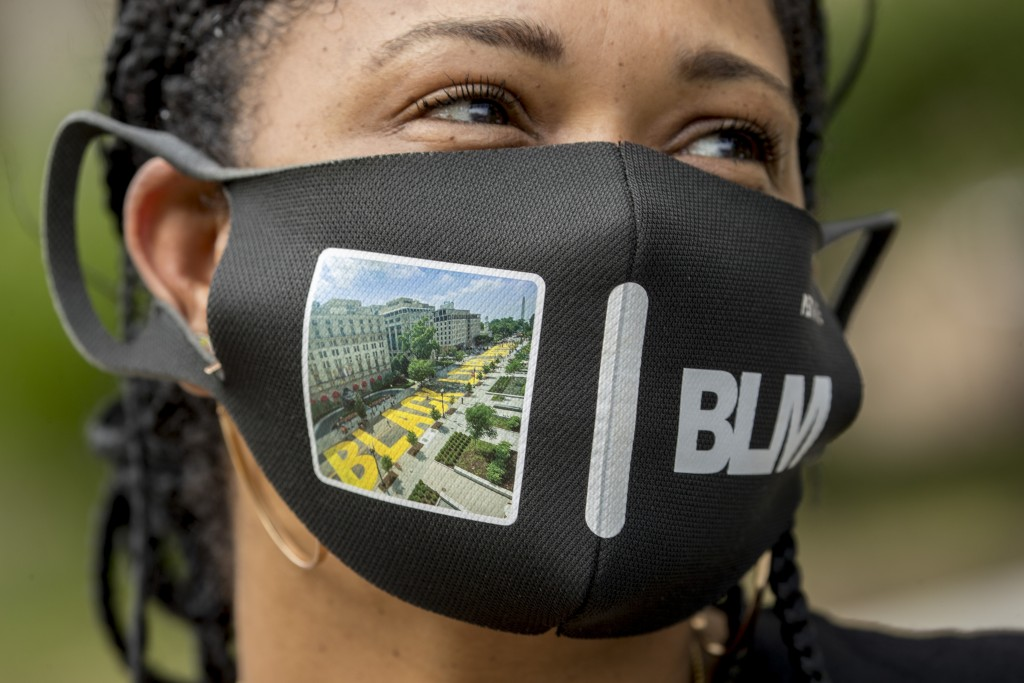 Shawna Jacobs of Fort Washington, Md., wears a mask with a photograph of 16th Street Northwest renamed Black Lives Matter Plaza near the White House, ...
