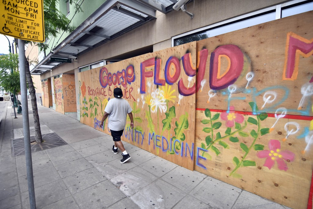 A pedestrian passes a colorful painted tribute to George Floyd on a boarded-up business, Thursday, June 18, 2020 in Minneapolis. Scores of businesses ...