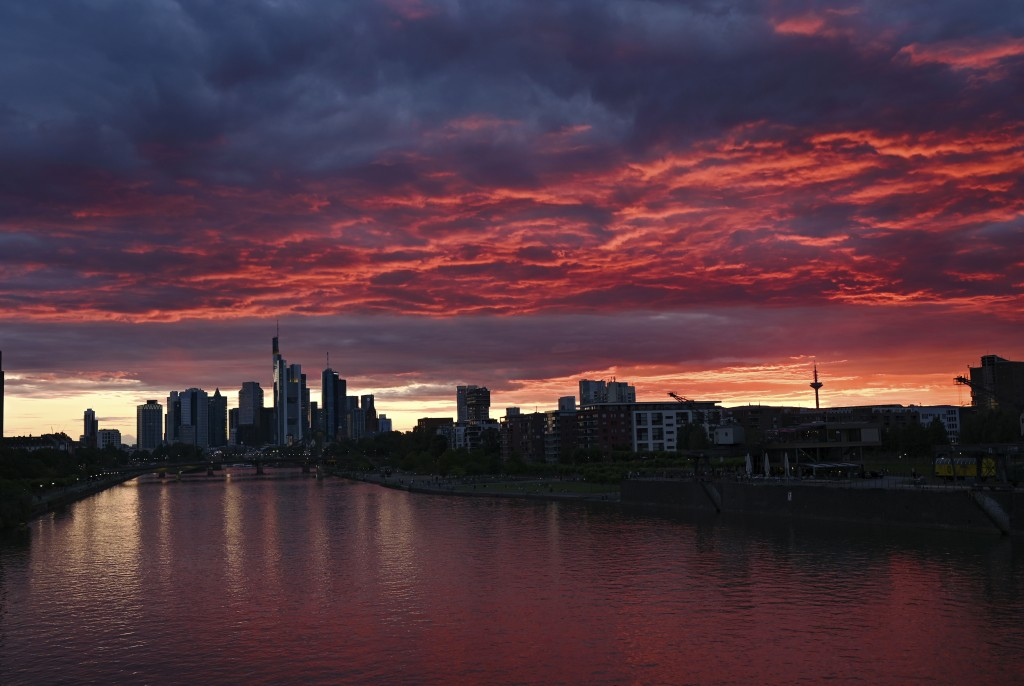 At sunset, the sky above the Frankfurt skyline and the water of the river Main are colored deep red, Friday, June 19, 2020, in Frankfurt, Germany. (Ar...
