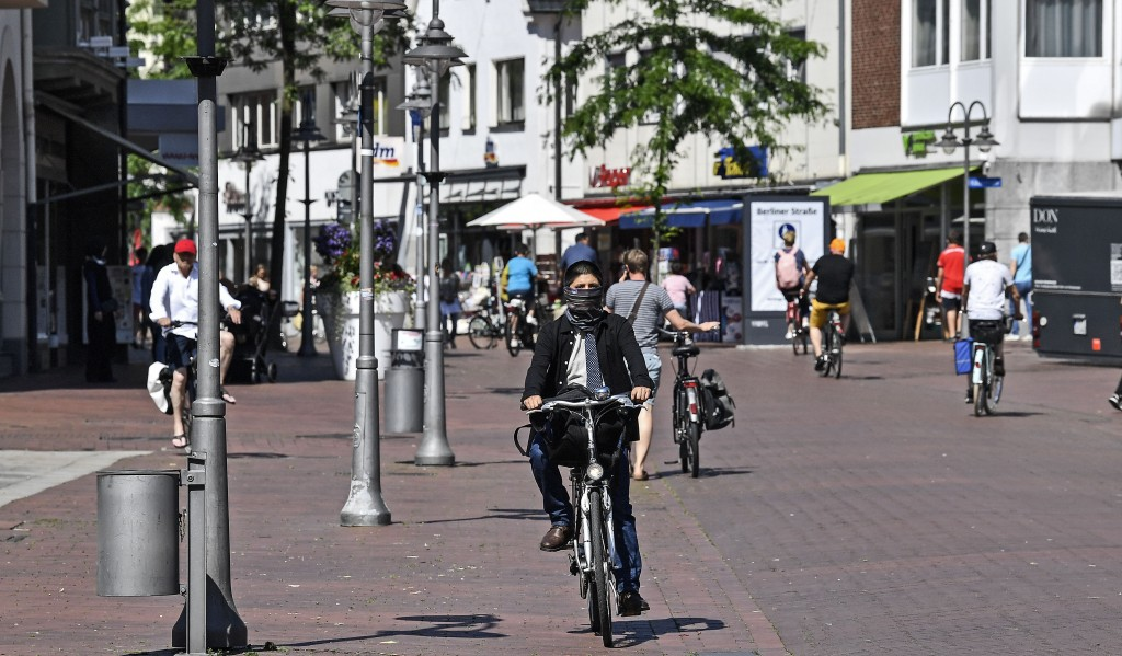 People on bicycles are pictured in the city center of Guetersloh, Germany, Tuesday, June 23, 2020. Following the corona outbreak at meat processor Toe...