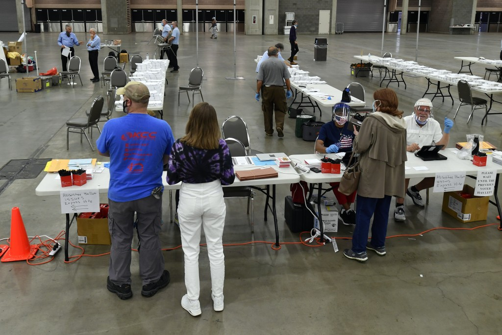 Voters register at their designated precinct to cast their ballot in the Kentucky primary at the Kentucky Exposition Center in Louisville, Ky., Tuesda...