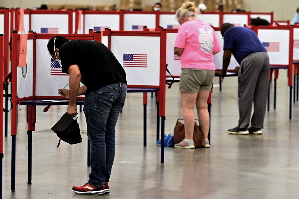 Voters fill out their ballots during in person voting in the Kentucky Primary at the Kentucky Exposition Center in Louisville, Ky., Tuesday, June 23, ...