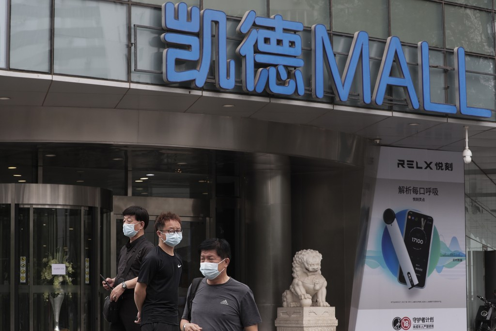 People wearing protective face masks to help curb the spread of the new coronavirus gather outside a shuttered shopping mall following positive cases ...