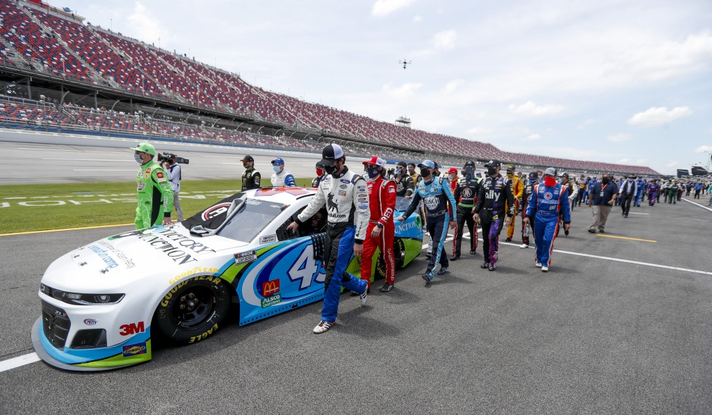 Nascar drivers Kyle Busch, left, and Corey LaJoie, right, join other drivers and crews as they push the car of Bubba Wallace to the front of the field...