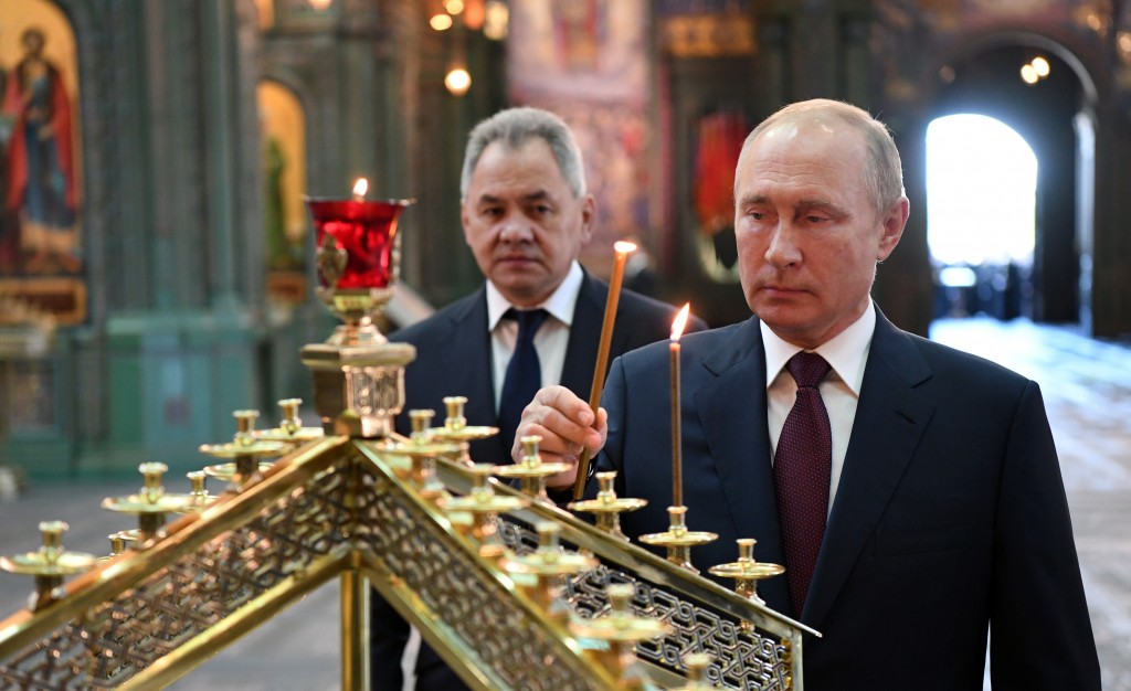 FILE - In this file photo taken on Monday, June 22, 2020, Russian President Vladimir Putin, right, with Russian Defense Minister Sergei Shoigu, lights...