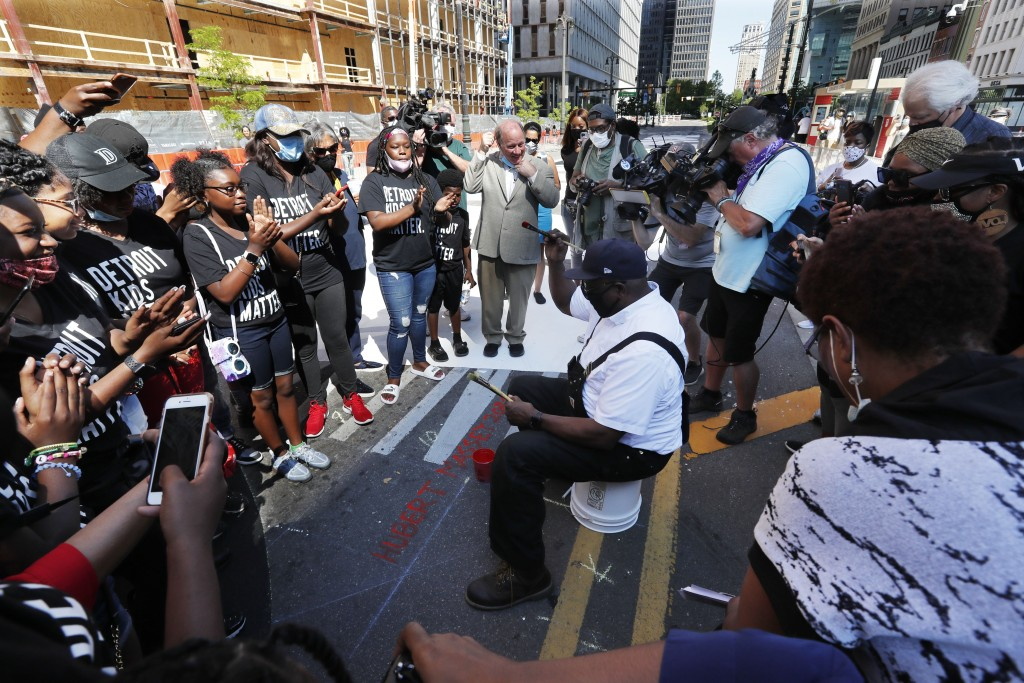 """Artist Hubert Massey raises a fist after signing his """"Power to the People"""" mural on Woodward Ave, Friday, June 19, 2020, in Detroit. The mural, funded..."""