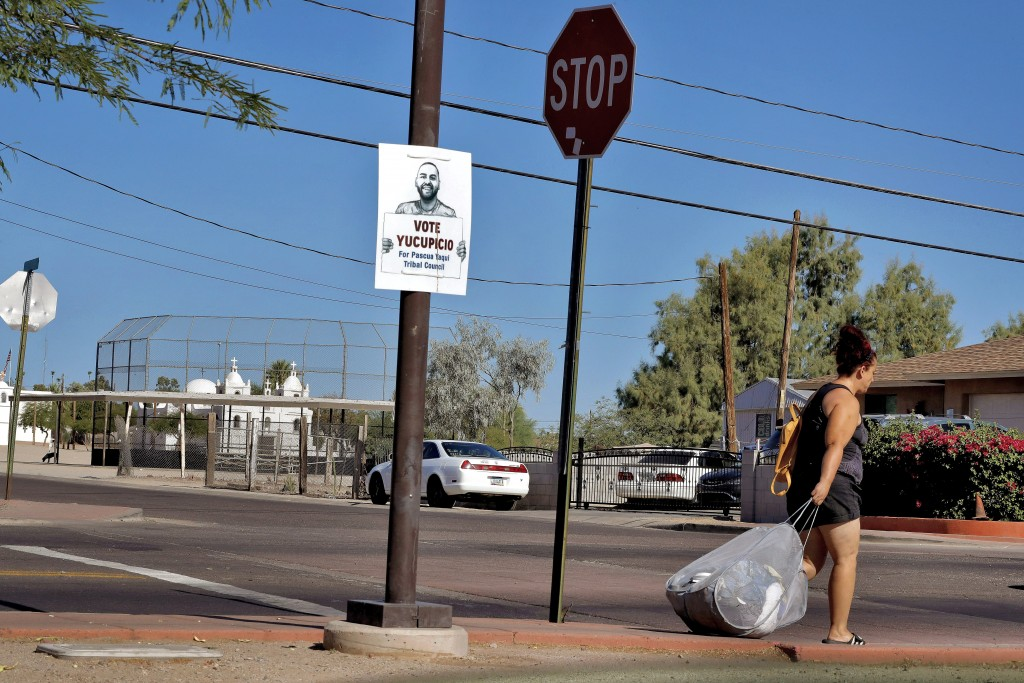 In this June 18, 2020, photo, a woman walks to a bus stop in Guadalupe, Ariz. As the coronavirus spreads deeper across America, it's ravaging through ...