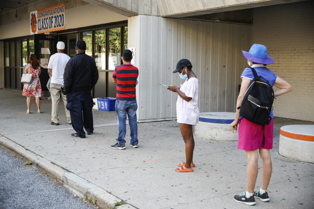 Voters wait in line to cast their ballots in New York's primary election at a polling station inside Yonkers Middle/High School, Tuesday, June 23, 202...