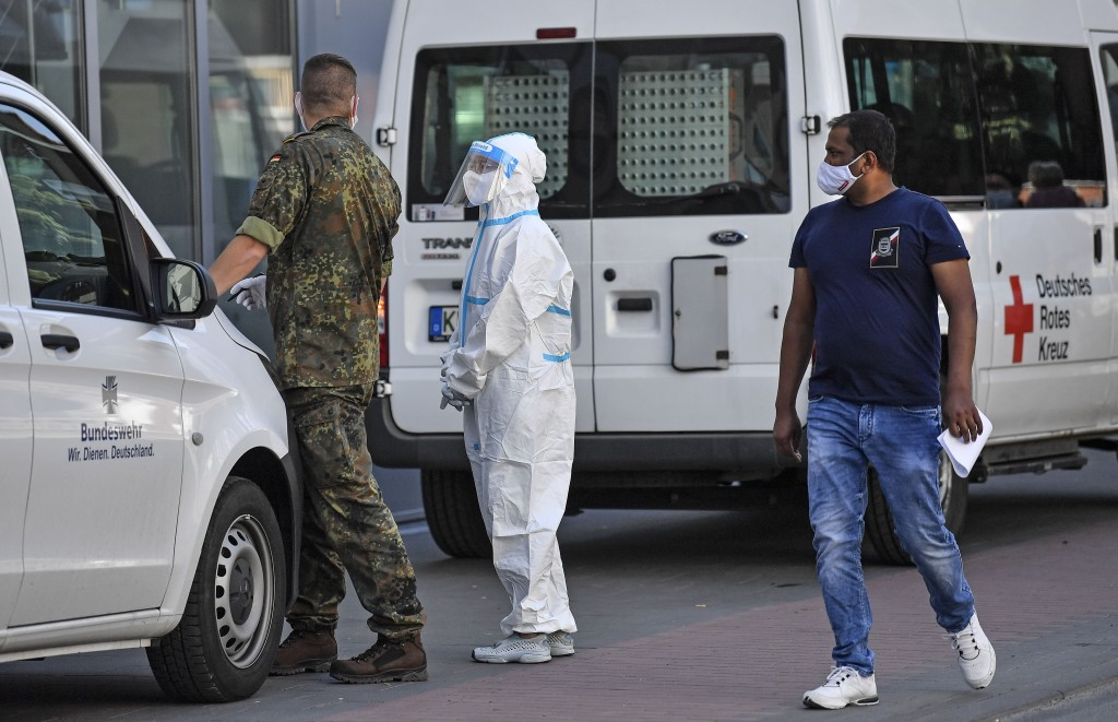 A pedestrian passes medical staff in the city center of Guetersloh, Germany, Tuesday, June 23, 2020. Following the corona outbreak at meat processor T...