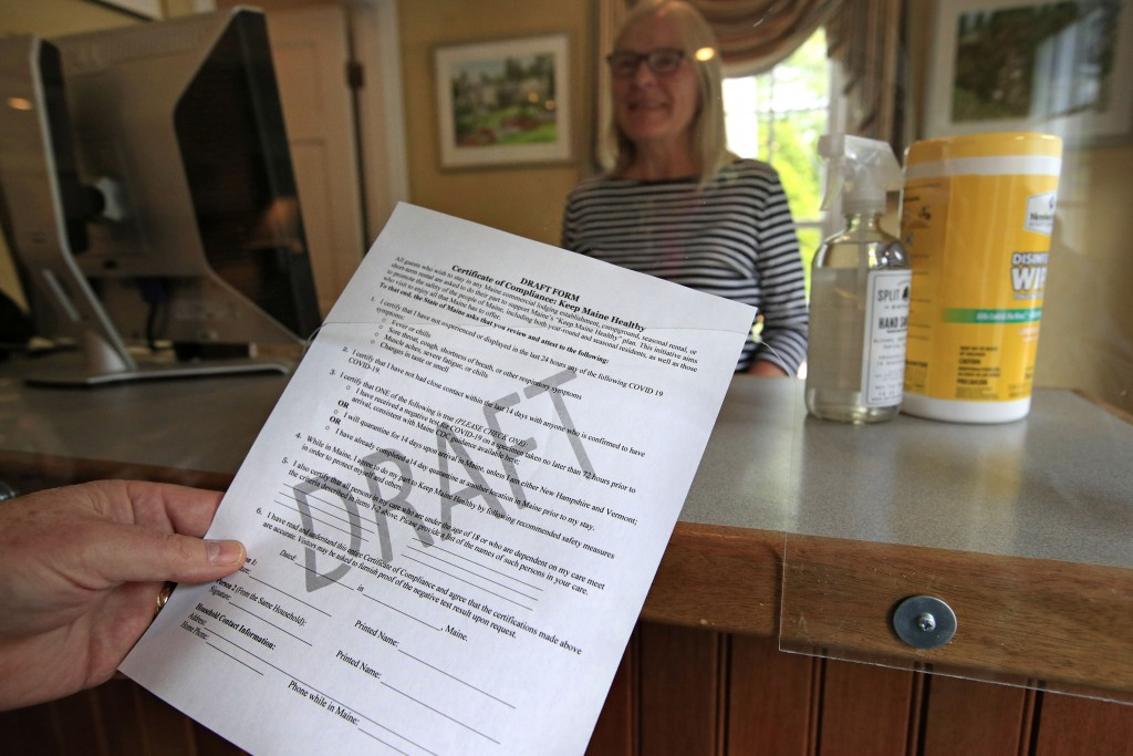 In this Wednesday, June 10, 2020, photo, a draft of a coronavirus pandemic compliance form is held by Cod Cove Inn owner Ted Hugger in Edgecomb, Maine...