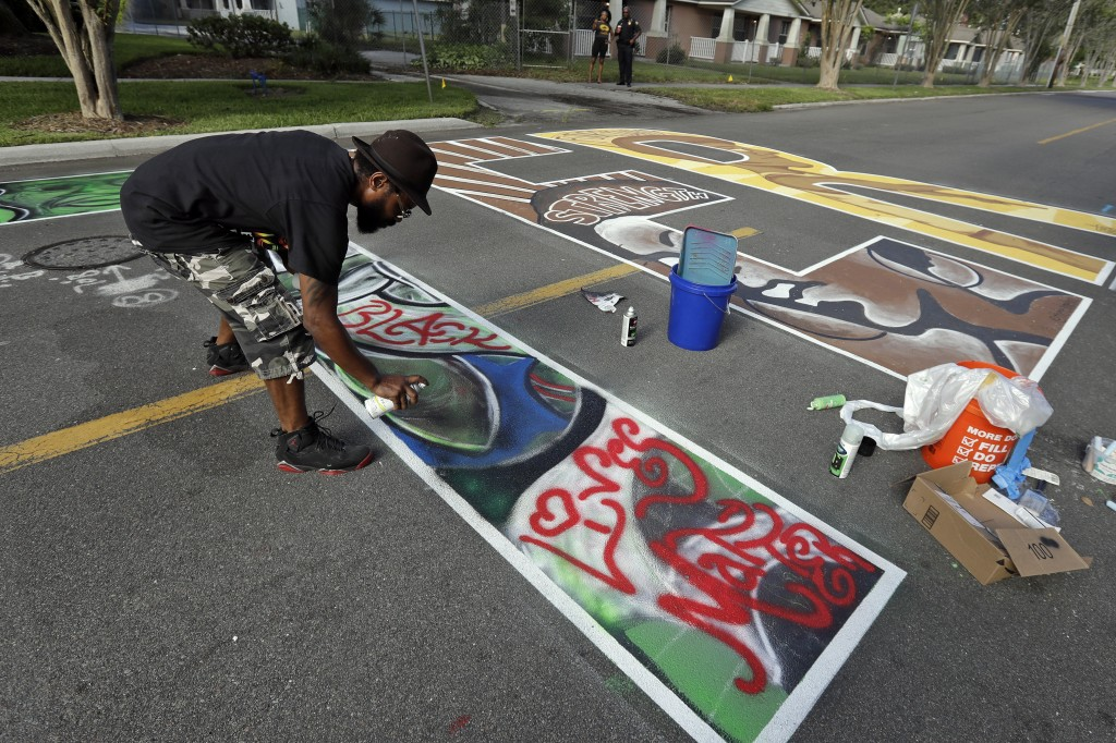 Local artist Plum Howlett puts the finishing touches on a letter of a Black Lives Matter mural during a Juneteenth 2020 celebration outside the Dr. Ca...