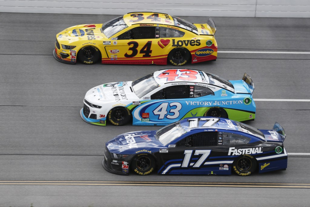 Michael McDowell (34), Bubba Wallace (43) and Chris Buescher (17) ride side-by-side during a NASCAR Cup Series auto race at Talladega Superspeedway in...