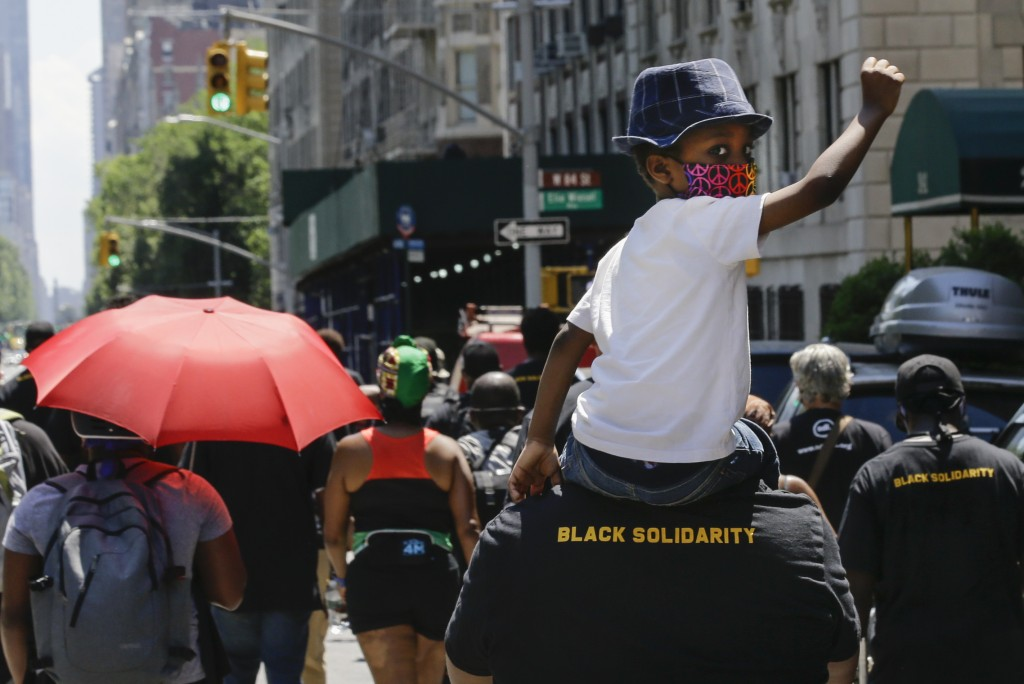 A man carries a child as they march near Central Park, during a Juneteenth celebration Friday, June 19, 2020, in New York. Juneteenth commemorates whe...