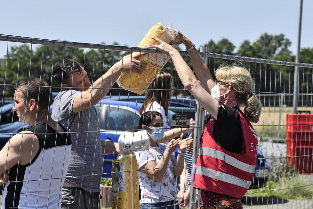 Helpers hand over diapers to Toennies employees and their families who are quarantined in their apartments behind fences in Verl, Germany, Tuesday, Ju...