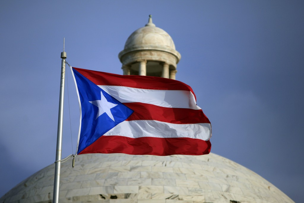 FILE - In this July 29, 2015 file photo, the Puerto Rican flag flies in front of Puerto Rico's Capitol as in San Juan, Puerto Rico. A federal control ...