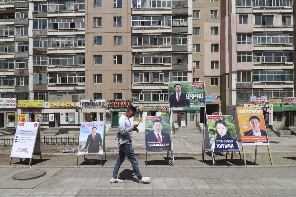 A man walks past election stands of various parties including ruling Mongolian People's Party and independent candidates in the Songinokhairkhan distr...