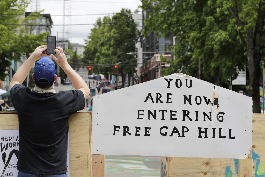 A man takes a photo over a blockade Sunday, June 21, 2020, in Seattle, where streets are blocked off in what has been named the Capitol Hill Occupied ...