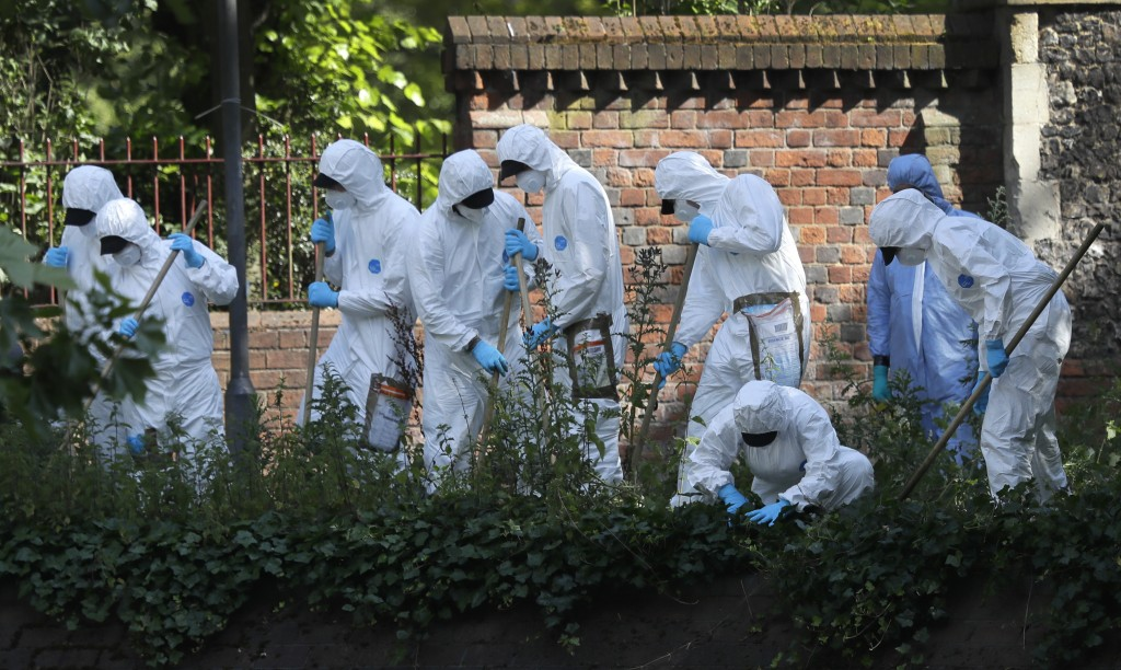 Police forensic officers search near the scene of a fatal multiple stabbing attack in Forbury Gardens, central Reading, England, Monday June 22, 2020....