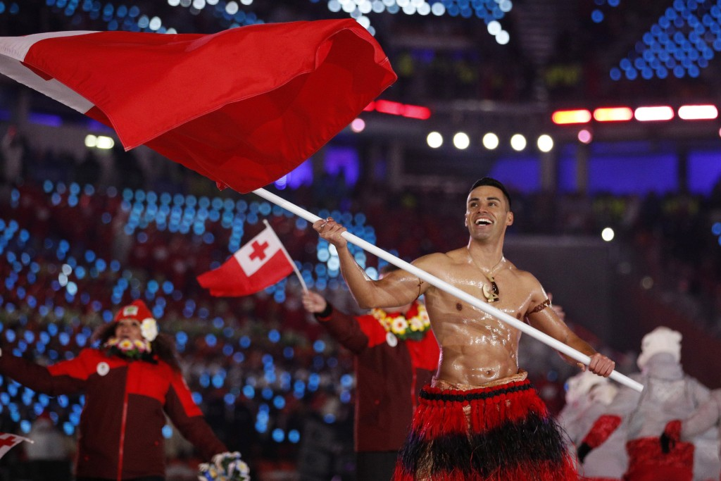 FILE - In this Feb. 9, 2018, file photo, Peta Taufatofua carries a flag of Tonga during the opening ceremony of the 2018 Winter Olympics in Pyeongchan...