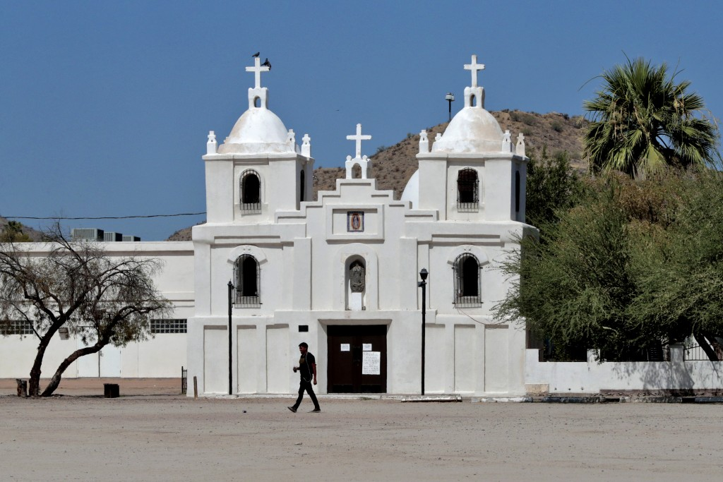 In this June 13, 2020, photo, a man walks past Our Lady of Guadalupe church in Guadalupe, Ariz. As the coronavirus spreads deeper across America, it's...