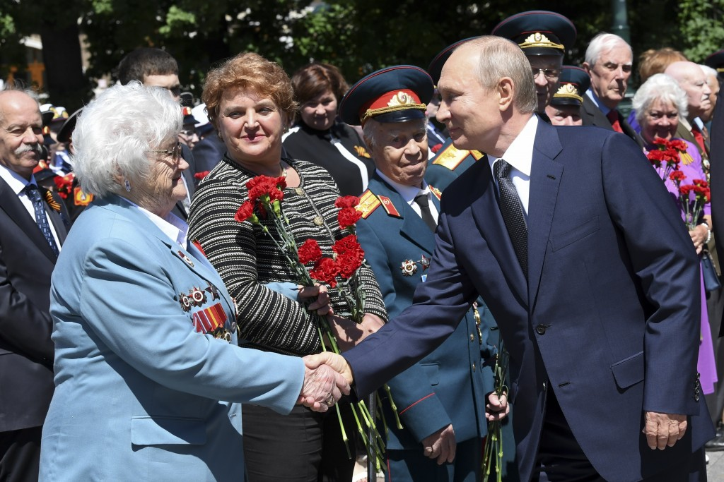 FILE - In this file photo taken on Monday, June 22, 2020, Russian President Vladimir Putin, right, greets a WWII veteran as he arrives to take part in...