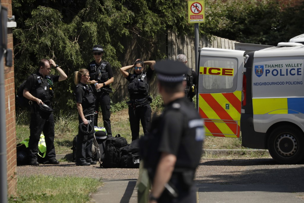 Police officers stand outside a building where a flat was being searched after a fatal multiple stabbing attack in Forbury Gardens park, in Reading, E...
