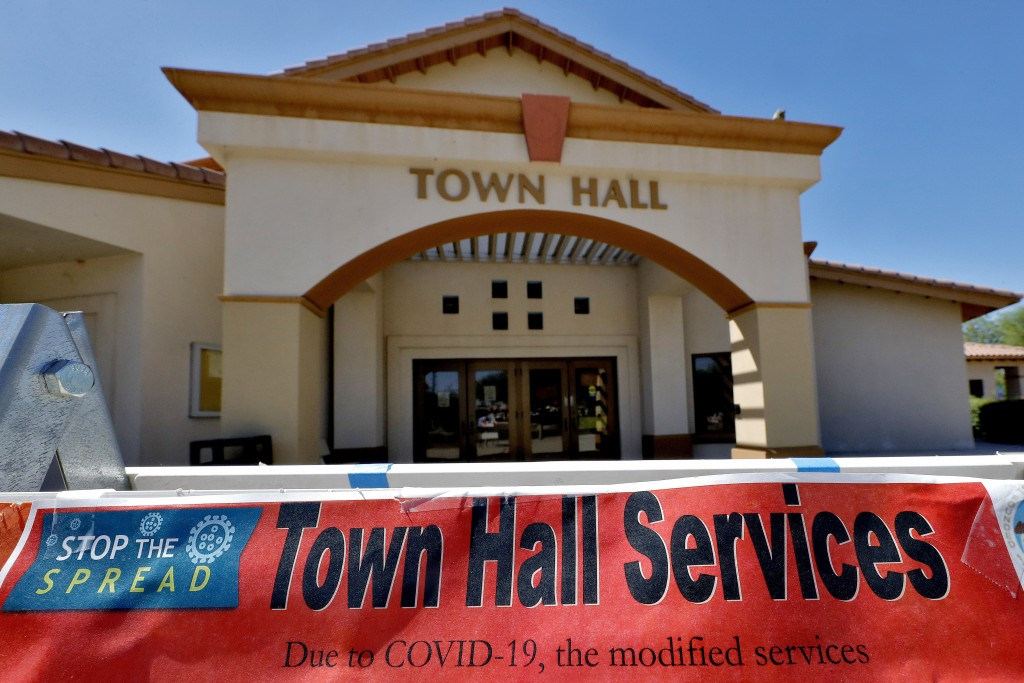 In this Thursday, June 18, 2020, photo, a sign in front of the Guadalupe Town Hall notifies visitors of modified services in Guadalupe, Ariz. As the c...