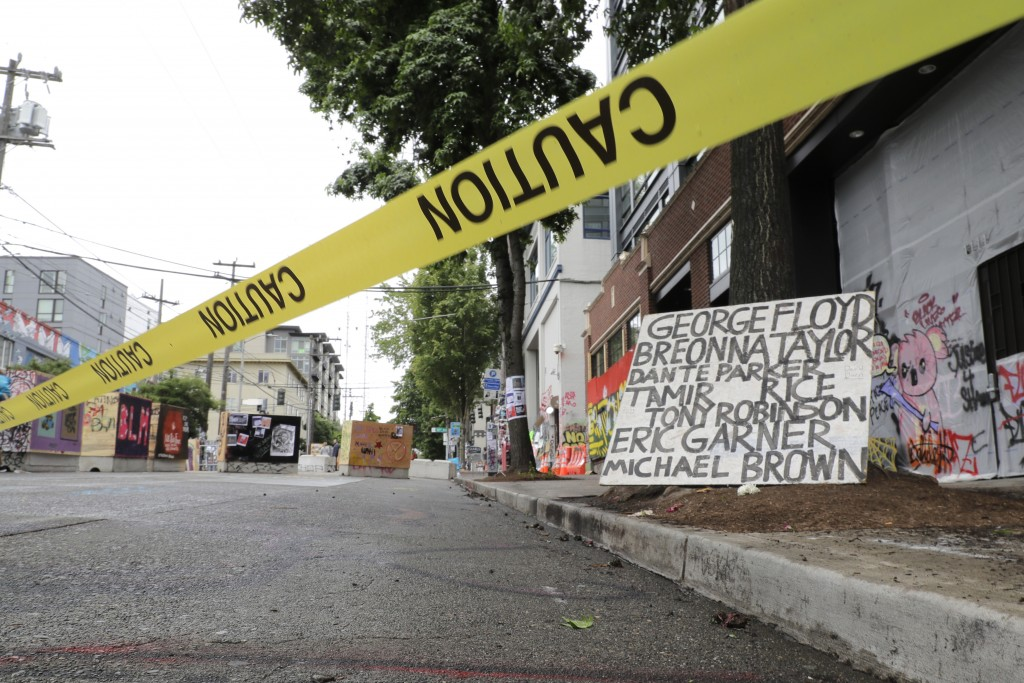 Caution tape is shown near a sign with the names of victims of police violence, Saturday, June 20, 2020, at the Capitol Hill Occupied Protest zone in ...