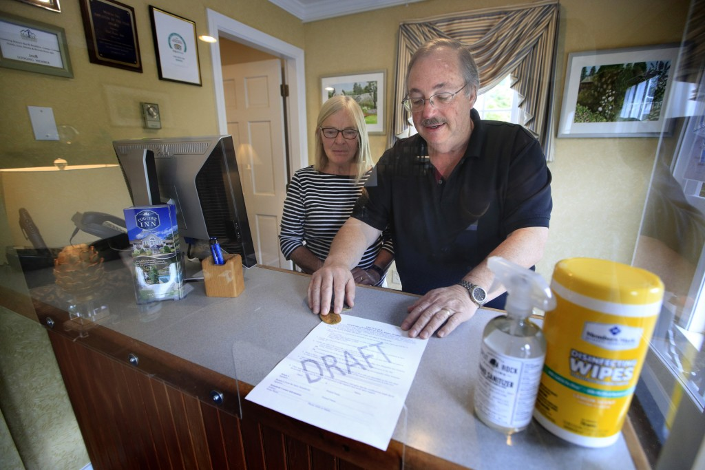 In this Wednesday, June 10, 2020, photo, Cod Cove Inn owners Ted and Jill Hugger show a draft of a compliance form that inn owners may be required to ...