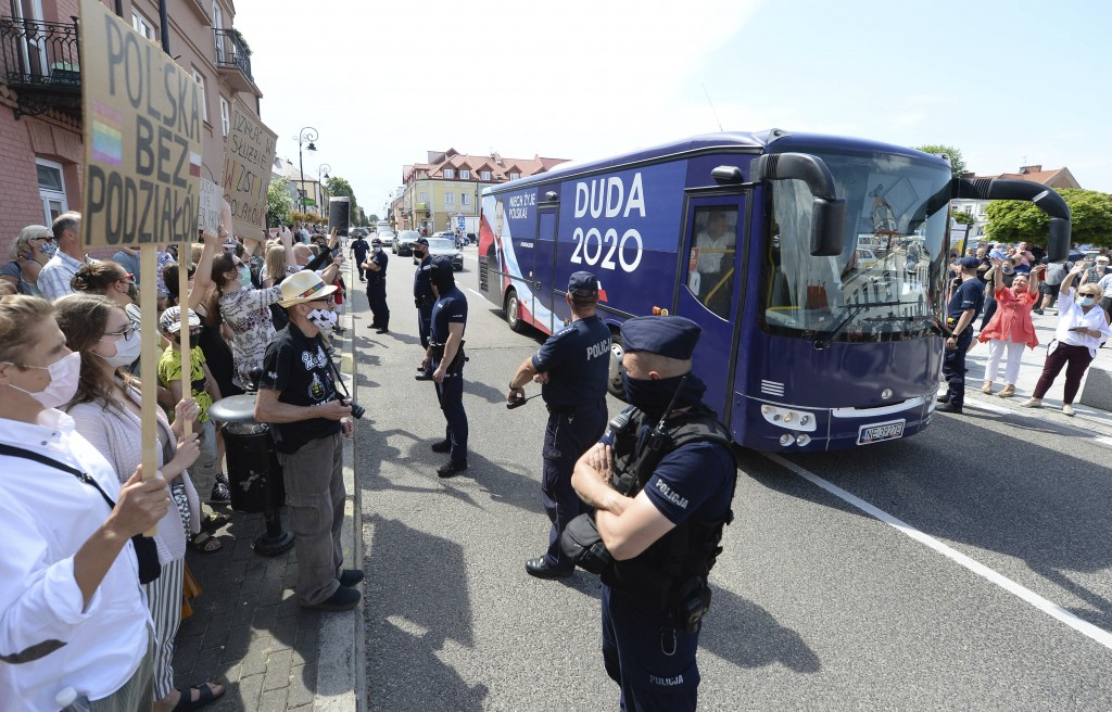 FILE - In this Wednesday, June 17, 2020 file photo, Pro-LGBT protesters greet the arrival of campaign bus of Polish President Andrzej Duda in Serock, ...