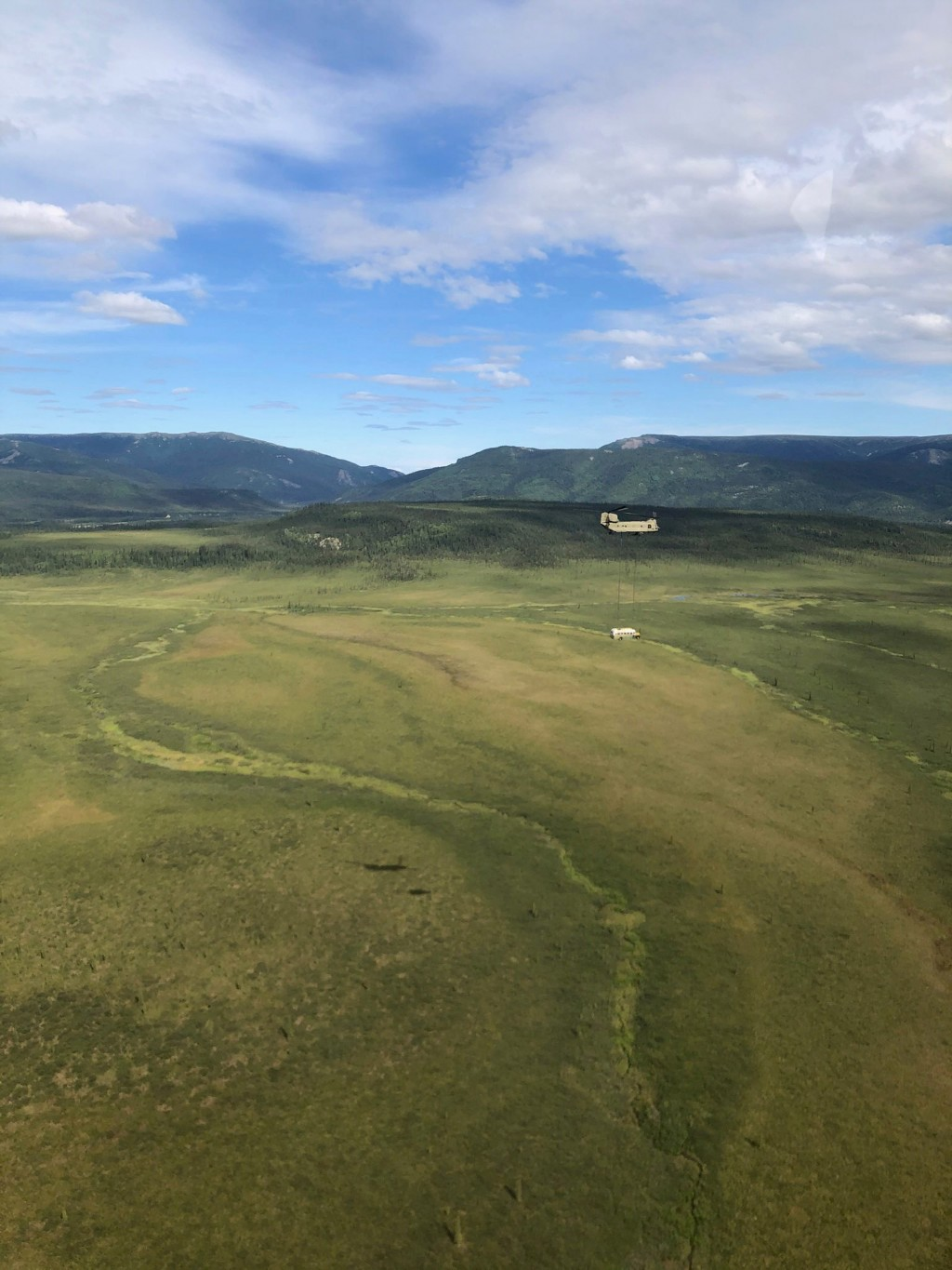 In this photo released by the Alaska National Guard, Alaska Army National Guard soldiers use a CH-47 Chinook helicopter to airlift an abandoned bus, p...