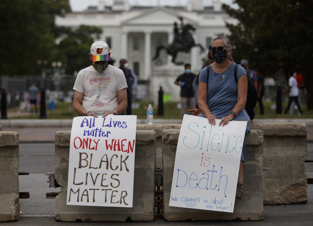 "Rick and Jayna Powell sit on a concrete barricade with signs the read ""All Lives Matter Only When Black Lives Matter"" and 'Silence is Death We Cannot ..."