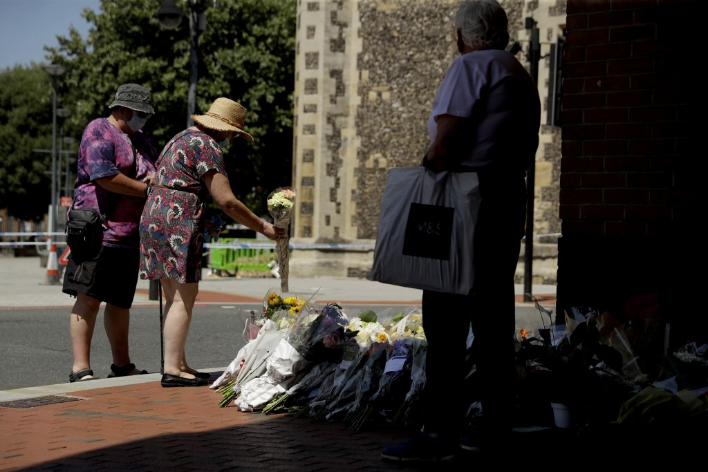 People place flowers by a police cordon near the scene of a fatal multiple stabbing attack at the Forbury Gardens park, in Reading, England, Tuesday, ...