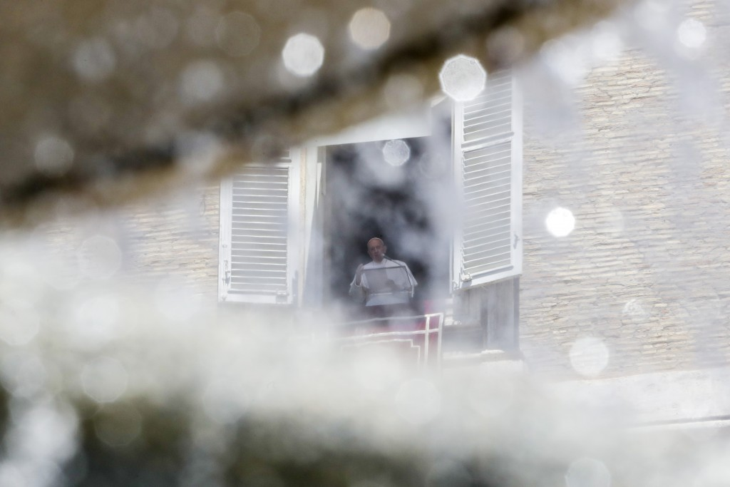 Pope Francis, framed by one the fountains that adorn St' Peter's Square, delivers his blessing as he recites the Angelus noon prayer from the window o...