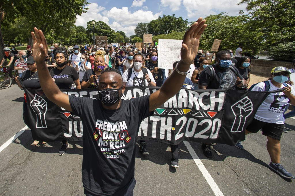 Malik Harris, left, leads protesters as they march towards the Martin Luther King Jr. Memorial in Washington on Friday, June 19, 2020, to mark Junetee...