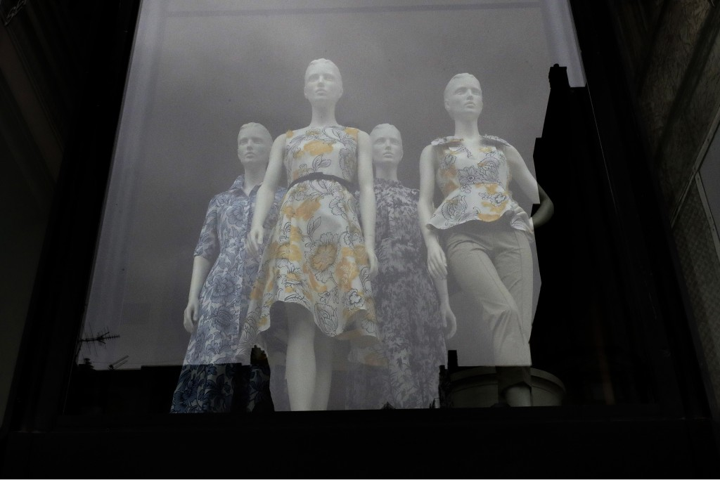 FILE - In this June 11, 2020, file photo garments are displayed on mannequins in a storefront window in Boston. Eighty-five percent of Democrats call ...