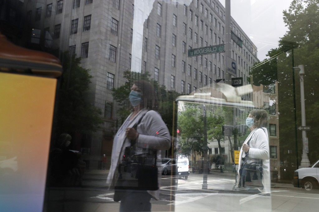 FILE - In this June 11, 2020, file a passer-by wears a mask out of concern for the coronavirus while walking past a storefront window in Boston. Eight...