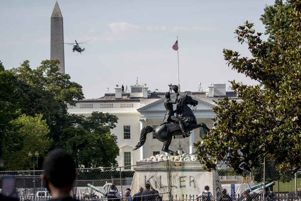 A presidential helicopter, the Washington Monument, and the White House are visible behind a statue of President Andrew Jackson in Lafayette Park, Tue...