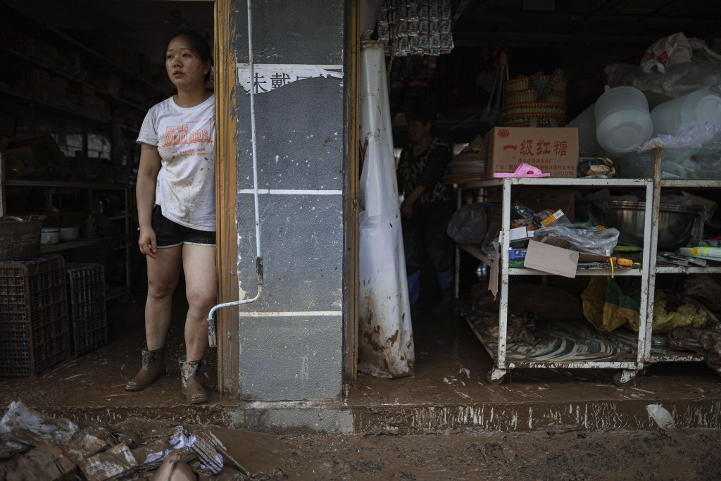 In this photo released by Xinhua News Agency a resident looks out from her flood damaged home in Bifeng Town of Zheng'an County in Zunyi, southwest Ch...
