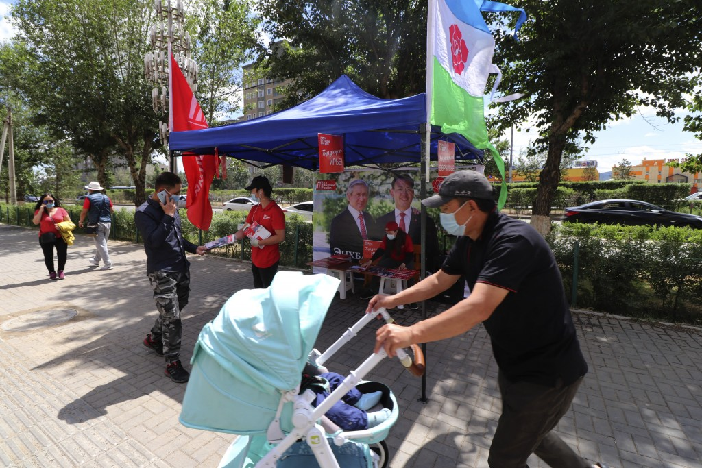 Election workers of Mongolian People's Revolutionary Party (MPRP) distribute election brochures on the downtown street of Ulaanbaatar, Mongolia, Monda...