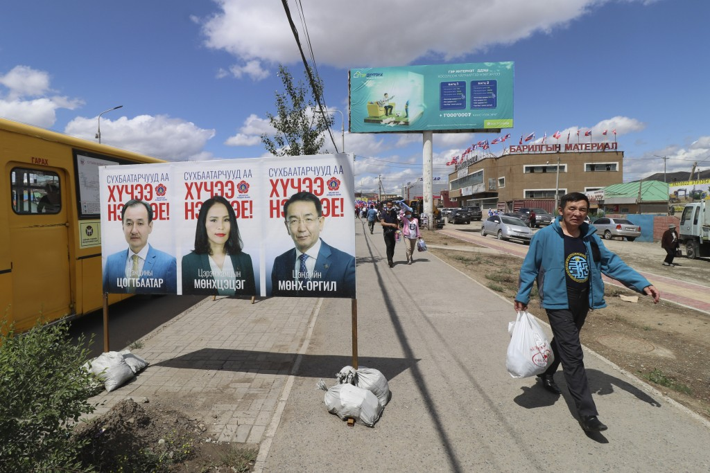 A man walks past an election poster of candidates of the ruling Mongolian People's Party (MPP) featuring current Foreign Minister Damdiny Tsogtbaatar,...