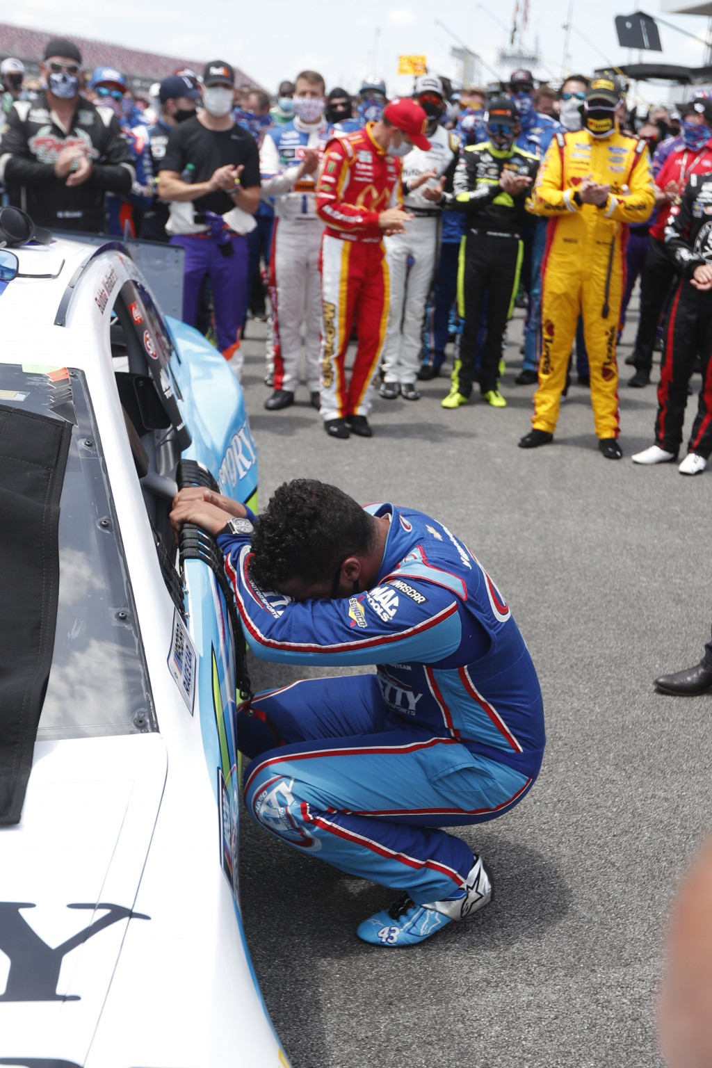Driver Bubba Wallace, front, is overcome with emotion as he arrives at his car in the pits of the Talladega Superspeedway prior to the start of the NA...