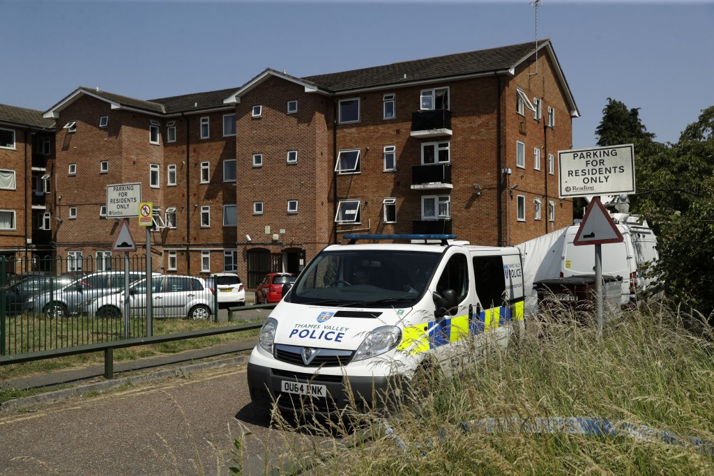 A police van sits parked outside a building where a flat was being searched after a fatal multiple stabbing attack in Forbury Gardens park, in Reading...