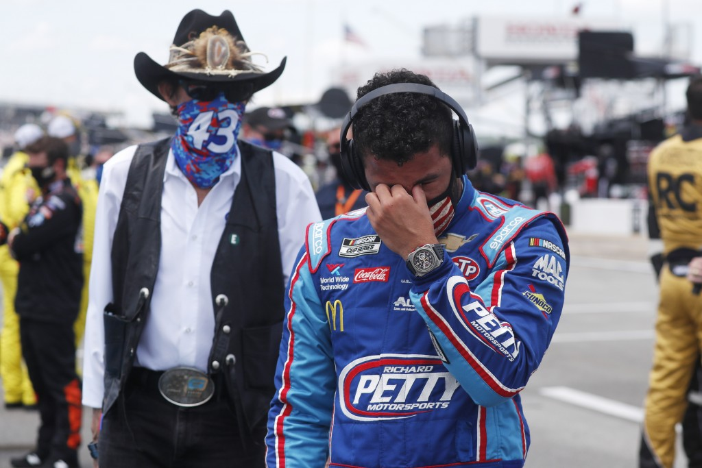 Driver Bubba Wallace, right, is overcome with emotion as he and team owner Richard Petty walk to his car in the pits of the Talladega Superspeedway pr...