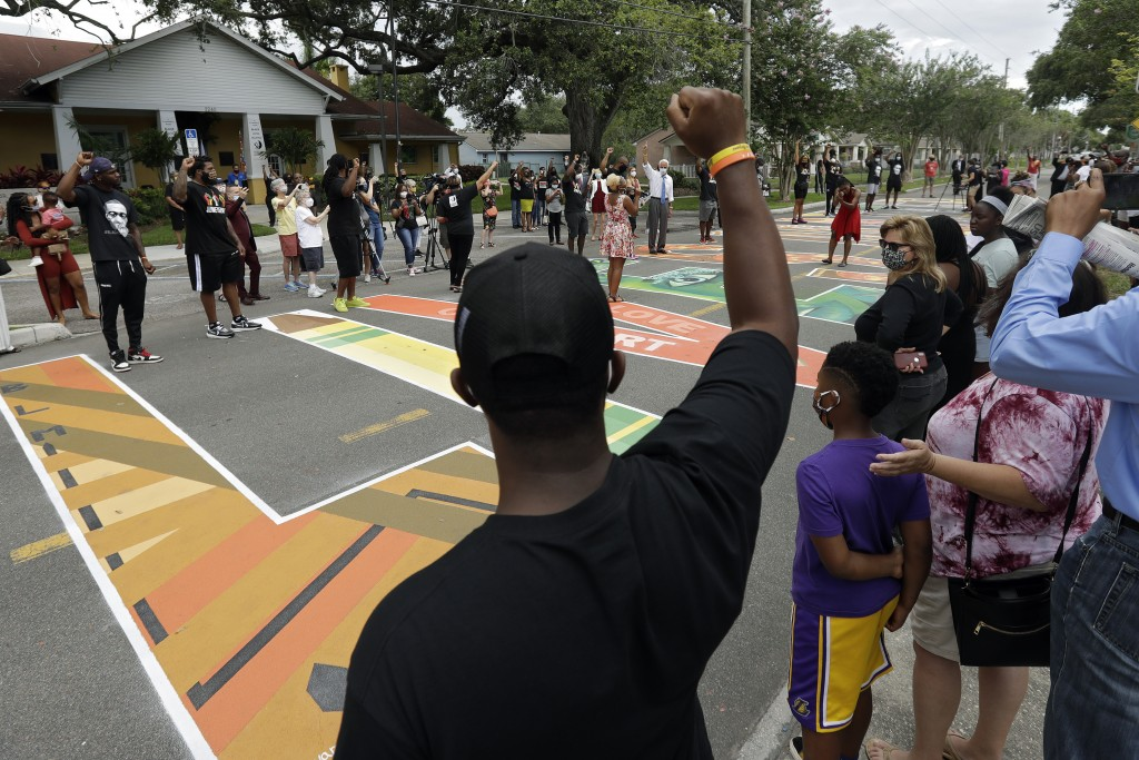 People raise their arms in solidarity as Sierra Davis Sanders and Ericka Still perform during a Juneteenth 2020 celebration outside the Dr. Carter G. ...
