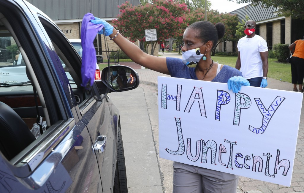 Kim Gardner distributes an aid bag during a drive through Juneteenth 2020 celebration in Dallas, Friday, June 19, 2020. Juneteenth marks the day in 18...
