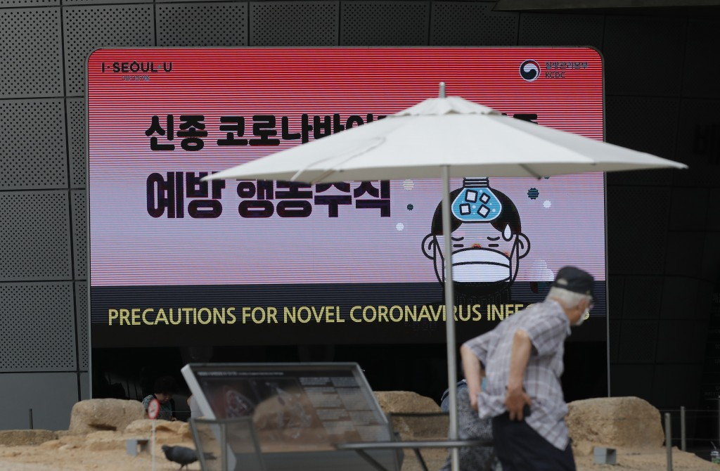 A visitor wearing a face mask walks near a screen displaying precautions against the coronavirus in Seoul, South Korea, Tuesday, June 23, 2020. (AP Ph...