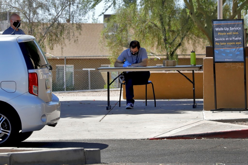 In this Thursday, June 18, 2020, photo, a man waits to check out books curbside from the Guadalupe library in Guadalupe, Ariz. As the coronavirus spre...