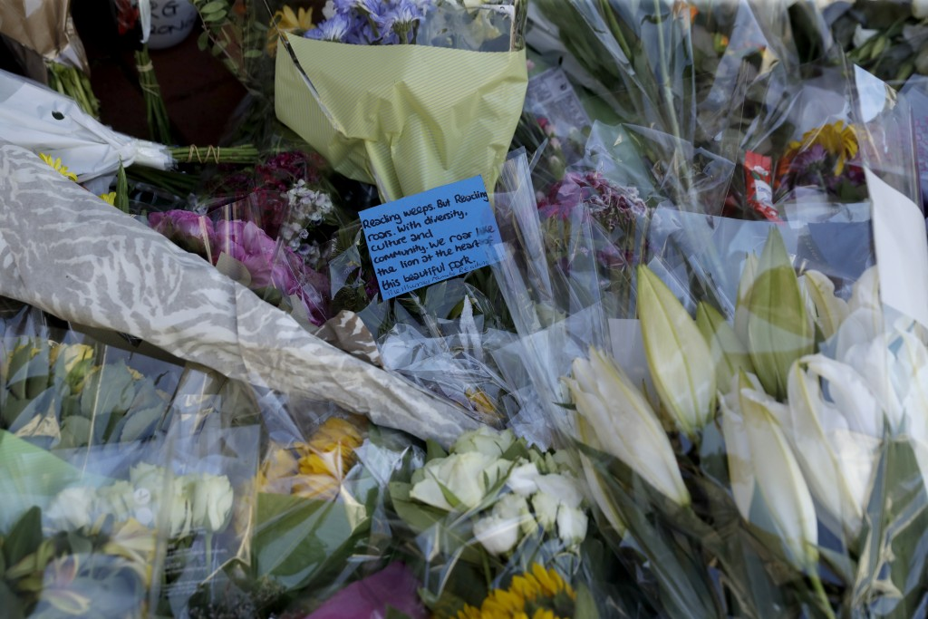 A written tribute lies with flowers placed beside a police cordon near the scene of a fatal multiple stabbing attack at the Forbury Gardens park, in R...